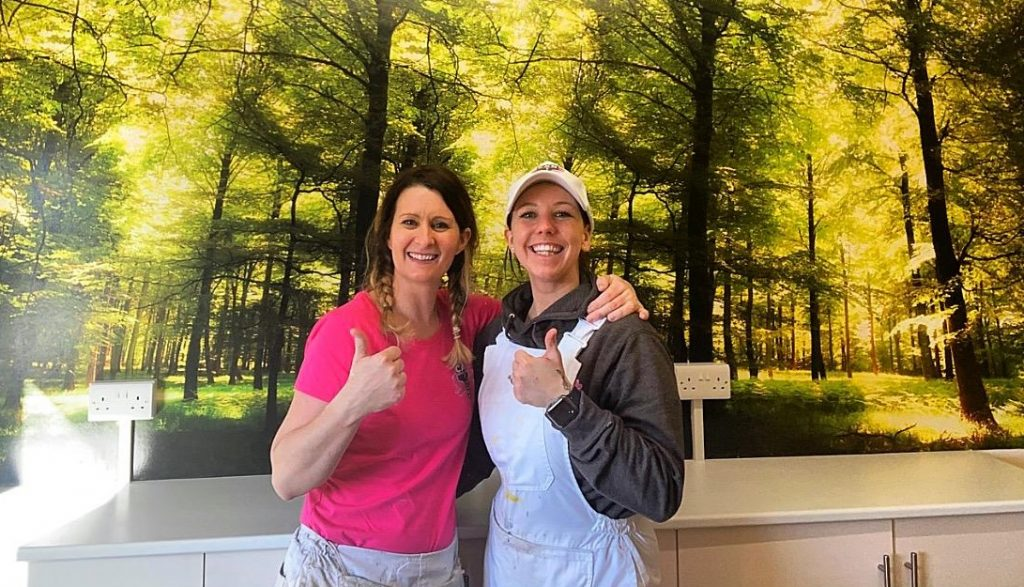 Sue and Courteney in front of a wall mural of a woodland scene they installed for a client